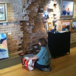 Brenda Orcutt hangs artwork at The Real Estate Studio