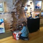 Brenda Orcutt hangs artwork at The Real Estate Studio