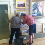 Marty Biernbaum hangs artwork at The Real Estate Studio