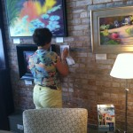 Patricia Huff hangs artwork at The Real Estate Studio