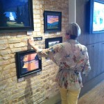 Mary Sayas Hanging Artwork at The Real Estate Studio