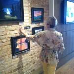 Mary Sayas Hanging Artwork at The Real Estate Studio